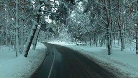 O zangão voa sobre a estrada através da floresta da neve do inverno Carro POV vídeos de arquivo
