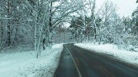 O zangão voa sobre a estrada através da floresta da neve do inverno Carro POV filme