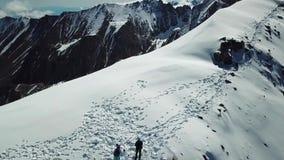 O zangão voa sobre a parte superior nevado do pico com povos e moscas ao penhasco video estoque