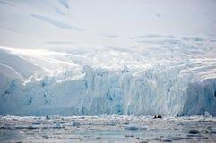 O zodíaco - minúsculo ao lado dos penhascos imensos do gelo - explora a baía do paraíso, imagem de stock royalty free