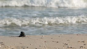 O zumbido apedreja a pirâmide na areia, na perspectiva das ondas do mar que simbolizam o zen video estoque