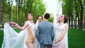 O zumbido fora dos jovens em trajes 'sexy' e os véus levantam para a sessão de foto vídeos de arquivo