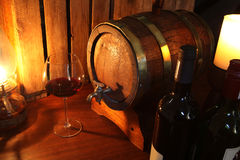 Wine cellar. Oak barrel and a glass and bottle of red wine stock photography