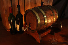 Wine cellar. Oak barrel and a glass and bottle of red wine royalty free stock images