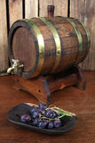 Wine cellar. Oak barrel and grapes ready for the wine making process royalty free stock photos