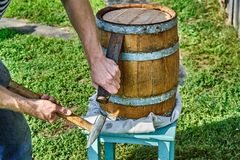 Oak Barrel. Opening the barrel with a chisel and hammer. Wooden barrel for 20 liters. Wooden barrel covered with wax. Opening the barrel with a chisel and hammer royalty free stock photos