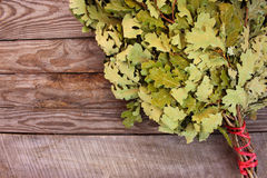 Oak broom for a bath on wooden background. Royalty Free Stock Images