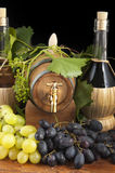 In oak casks with vines and grapes white and black Royalty Free Stock Images