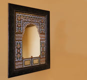 Oak framed indigenous mosiac mirror India. Rajasthan, India, square oak framed indigenous mosaic mirror mounted on a magnolia emulsion painted wall Royalty Free Stock Photos