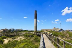 Oak Island Lighthouse. Painted black, white and gray, is located on Caswell Beach in North Carolina. Shot take from the boardwalk across the street leading to royalty free stock photography