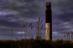 Oak Island Lighthouse stands in front of stormy skies stock image