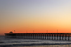 Oak Island NC Pier at Sunset. Oak Island North Carolina pier at sunset with lots of room for text in horizontal format.  Could easily be a panoramic Royalty Free Stock Photography