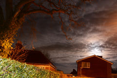 Oak Tree and Full Moon. An old oak tree looks dramatic at night during a full moon and epic cloudscape Stock Photo