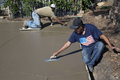 Oak View, California, USA, October 18, 2014, Hispanic concrete workers spread wet concrete for driveway Stock Photos