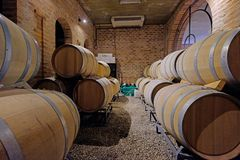 Oak wine barrels in the cellar of a Malbec winery factory in San Juan, Argentina, South America, also seen in Mendoza. Oak wine barrels stacked in the cellar of stock photos