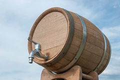 Oak wine cask. With metal tap on blue cloudy sky background from lower angle royalty free stock images