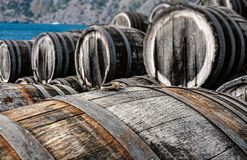 Oak wine casks on winery. A lot of oak wine casks with madeira wine while maderization on solarium with mountain and sea on background Royalty Free Stock Image