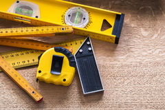 Oaken board with wooden meter measuring line. Construction level and square ruler maintenance concept Stock Photos