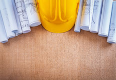 Oaken wooden board with building helmet and. Blueprints construction concept Royalty Free Stock Photos