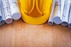 Oaken wooden board with building helmet and heap. Of construction drawings repairing concept Stock Photography