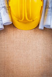 Oaken wooden board with yellow hard hat and. Blueprints construction concept Stock Images