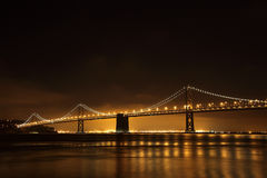 Oakland Bay Bridge at Night. With gloing fog over commercial doc and shipping loading cranes  in background, spanning San Francisco Bay, California Royalty Free Stock Image