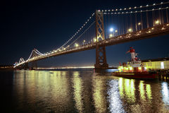 Oakland Bay Bridge  in San Francisco at night. Oakland Bay Bridge and pusher boat in San Francisco at night Stock Photography