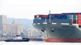 Cargo Ship HAMBURG BRIDGE departing the Port of Oakland. Oakland, CA - December 13, 2016: Tugboat PATRICIA ANN at the bow of cargo ship HAMBURG BRIDGE maneuver Royalty Free Stock Image