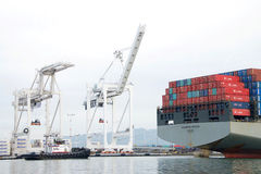 Cargo Ship HAMBURG BRIDGE departing the Port of Oakland. Oakland, CA - December 13, 2016: Tugboat REVOLUTION at the stern of HAMBURG BRIDGE, assisting the vessel Royalty Free Stock Images