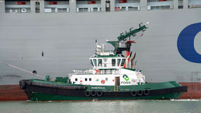 Tugboat AMERICA assisting cargo ship COSCO FORTUNE maneuver Stock Photography