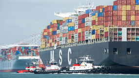 Cargo Ship MSC ARIANE entering the Port of Oakland. Oakland, CA - September 12, 2016: Cargo Ships are not able to maneuver sideways. Tugboats VETERAN, REVOLUTION Stock Image