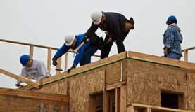 Men build roof for home for Habitat For Humanity royalty free stock image