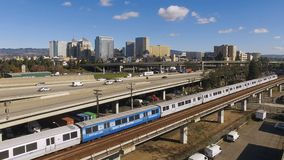 Oakland California Downtown City Skyline Highway Train Mass Transit. People travel via trains and autos in Oakland California at rush hour stock footage