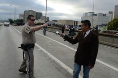 Oakland Protest. California Highway Patrol and News Reporter fighting on Interstate 880. Get off the, freeway! This is your fault!!!! -CHP to News Reporter Stock Photo