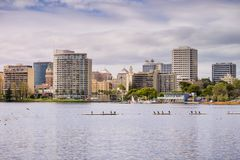 Oakland van de binnenstad zoals die van over Meer Merritt op een bewolkte de lentedag wordt gezien Stock Foto