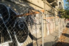 Oakland, verlaten brandwond die met graffiti en de omheining van de kettingsverbinding uitbouwen stock foto's