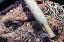 Oar and fishing nets. Detail of an oar and dry fishing nets waiting to be used stock photos