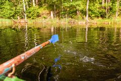 Oar paddle from row boat. Closeup of oar paddle from row boat moving in water on green lake with ripples. Camping tourism relax trip active lifestyle adventure stock image