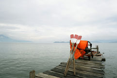 Oars and life jackets on jetty. A cart carrying three oars and several life jackets rests on a wooden jetty Royalty Free Stock Photography