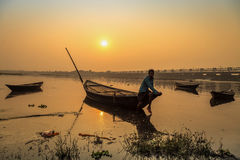 An oarsman sits on his boat to shore at sunset on river Damodar near the Durgapur Barrage. DURGAPUR, INDIA - DECEMBER 20, 2016: An oarsman sits on his boat to stock photography