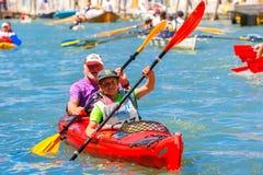 Oarsmen in the Venice Vogalonga regatta, Italy. Venice, Veneto, Italy - May 24, 2015: Boy and man oarsmen, in red boat race along the Cannaregio Canal in the Stock Image