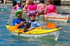 Oarsmen in the Venice Vogalonga regatta, Italy. Venice, Veneto, Italy - May 24, 2015: Man and woman oarsmen in colorful hats in boat race along the Cannaregio Stock Image