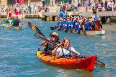 Oarsmen in the Venice Vogalonga regatta, Italy. Venice, Veneto, Italy - May 24, 2015: Man and woman oarsmen, in an orange boat race along the Cannaregio Canal Stock Photography