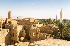 Oase, ruïnes van oude Arabische die stad van het Middenoosten van modderbakstenen wordt gebouwd, oude moskee, minaret Al Qasr, Da stock fotografie