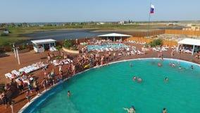 Oashandfatet i byn av Golubitskaya, Krasnodar territorium Folket är avslappnande i pölen Simbassäng för vuxna människor och lager videofilmer