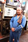 Oasis de Dakhla, Egipto - 3 de abril de 2015: Un empleado local presenta delante de una máquina expendedora vieja del gas Imagenes de archivo