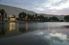 Oasis in eveninglight. Oasis Huacachina, near Ica, Peru a wonderful little lake with palmtrees, walled of high sand dunes royalty free stock image