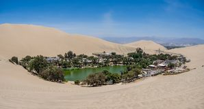 Oasis of Huacachina near Ica city in Peru. Lake and trees inside the dunes stock photography