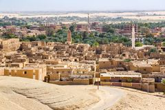 Oasis with ruins. Ancient middle eastern Arab town built of mud bricks, old mosque, minaret. New city in back. Al Qasr, Dakhla, stock photography