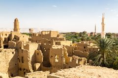 Oasis, ruins of ancient middle eastern Arab town built of mud bricks, old mosque, minaret. Al Qasr, Dakhla, Western Desert, Egypt. stock photography